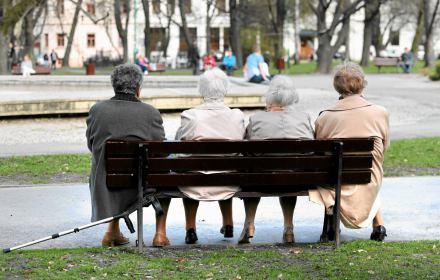 Emerytki siedzące na ławce w parku.