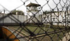 Zdjęcie przedstawia budynek więzienia widoczny zza krat