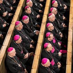 Biskupi siedzą w kościelnych ławach
