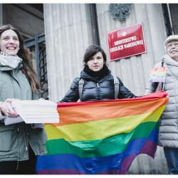 Na zdjęciu: Trzy osoby pod budynkiem Ministerstwa Edukacji Narodowej z tęczową flagą