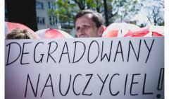 Na zdjęciu nauczyciel podczas protestu pod MEN z transparentem: