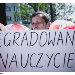 """Na zdjęciu nauczyciel podczas protestu pod MEN z transparentem: """"Degradowany nauczyciel"""""""