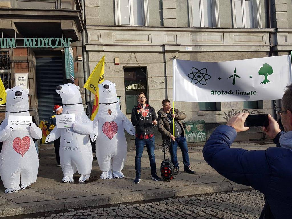 Kilka osób w przebraniach niedzwiedzi polarnych z transparentem