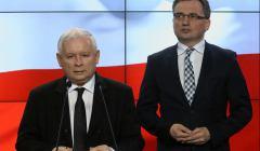 Stoją Jarosław Kaczyński stoi przy mównicy, z tyłu Zbigniew Ziobro
