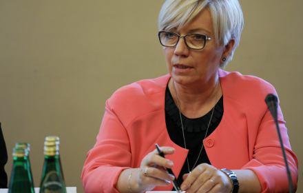 Na zdjęciu Julia Przyłębska siedzi w różowym żakiecie, w ręku trzyma długopis