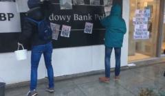 """Dwie osoby przyklejającą plakaty na tablicy z napisem """"NBP. Narodowy Bank Polski"""". Hasło na jednym z plakatów brzmi: """"Art. 54 Konstytucji: Cenzura prewencyjna jest zakazana. Prawdy nie zakneblujesz""""."""
