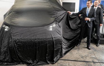 Mateusz Morawiecki ściąga pokrowiec z auta z elektrycznym silnikiem. Auto to plastikowy model