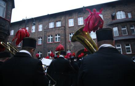 Orkiestra górnicza w galowych mundurach maszeruje ulicami Nikiszowca