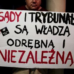 """Mężczyzna trzyma plakat """"Sądy i trybubały są władzą odrębną i niezależną"""""""