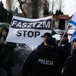"""Grupa osób trzyma banery """"Faszyzm Stop"""" i flagi Izraela"""
