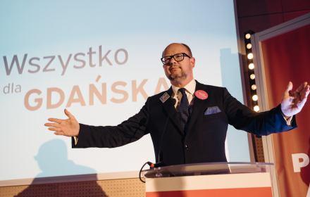 Paweł Adamowicz stoi na scenie z szeroko otwartymi ramionami