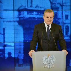 Piotr Gliński stoi przy mównicy na tle fotografii budynku szpitala Bersohnów i Baumanów