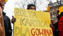 Protestujący trzyma przed sobą żółty baner z napisem