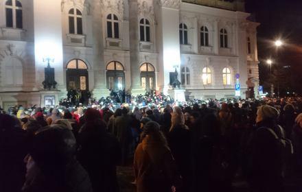 Demonstranci zgromadzeni przed gmachem Zachęty, wieczór, fasada gmachu mocno oświetlona