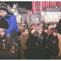 Mężczyzna trzyma na ramionach chłopczyka, w tele duży tłum demonstrantów
