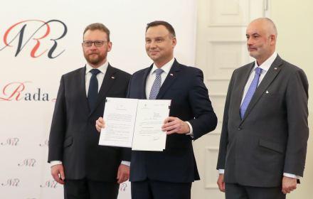 Andrzej Duda w towarzystwie ministra zdrowia Łukasza Szumowskiego pokazuje podpisany przez siebie projekt Narodwej Strategii Onkologicznej