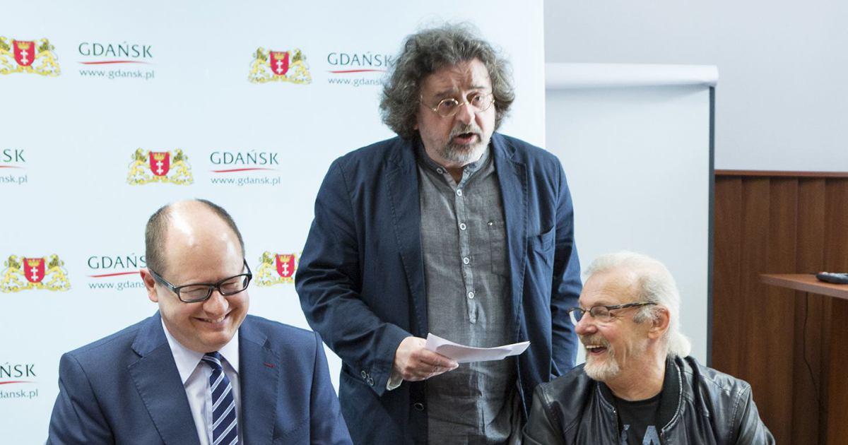 Paweł Adamowicz siedxzi uśmiechnięty, obok stoi jego ówczesny rzecznik Antoni Pawlak