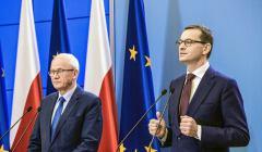 Minister Tchórzewski obok gestykulującego premiera Morawieckiego podczas konferencji prasowej w grudniu 2018