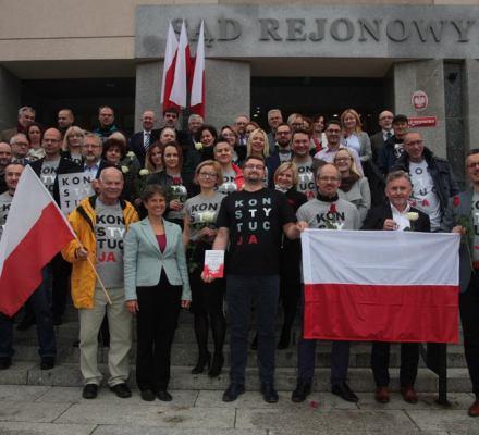 Uśmiechnięci sędziwoie stoją przed wejsćiem do Sądu Rejonowego w Olsztynie w koszulkach z napisem Konstytucja