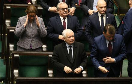 Jarosłąw Kaczyński stoi na swoim miejscu poselskim w Sejmie, patrzy w góre na wynik głosowania. Wokół niego Beata Mazurek i Mariusz Błaszczak