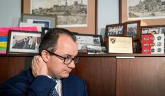Adam Bodnar w biurze , w tle obrazy