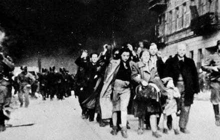 Likiwdacja getta warszawskiego, idzie tłum ludzi z podniesionymi rękami w otoczeniu uzbrojonych Niemców, w tle dymy palącego się getta w Warszawie