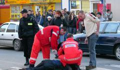 Potrącona przez samochód osoba leży na pasach, ratownicy w czerwonych kombinezonach pomagają ofierze