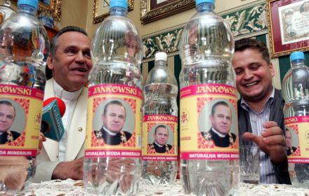ks. Jankowski prezentuje butelki z wodą mineralną ze swoją podobizną