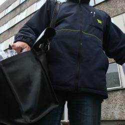 Listonosz z ciężką torbą, w której ledwo mieszczą się listy.