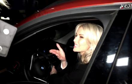 Magdalena Ogórek siedzi w samochodzi, okno otwarte i przesyła całusy protestującym pod TVP