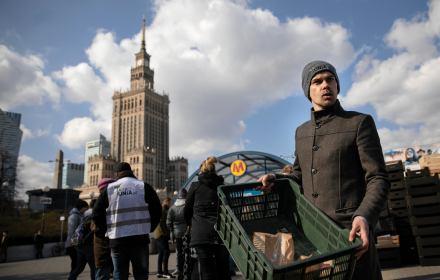 Michał Kołodziejczak, lider AgroUnii, trzyma skrzynkę z jabłkami podczas protestu w Warszawie przy metrze Centrum