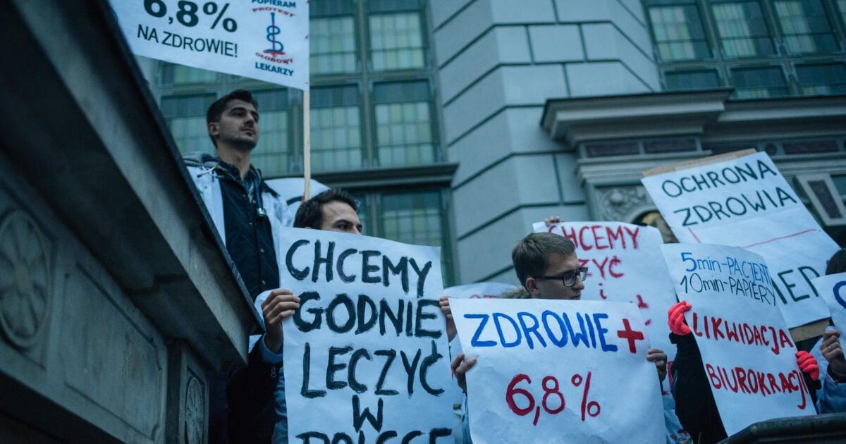 """Lekarze rezydenci trzymają plakat z napisem""""Chcemy godnie leczyć w Polsce"""""""