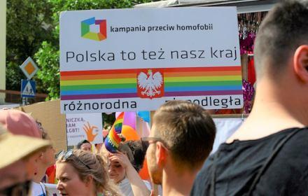 """Młodzi ludzie na tle baneru """"Polska to też nasz kraj"""" z kolorami tęczy"""