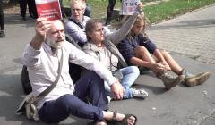 Kilka osób, Obywateli RP, siedzi na ziemi i trzyma w rękach konstytucję