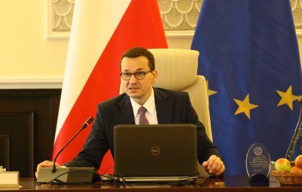 Mateusz Morawiecki za biurkiem, przed nim otwarty laptop