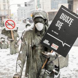 Statua w masce przeciwsmogowej z banerem z napisem Duszę się