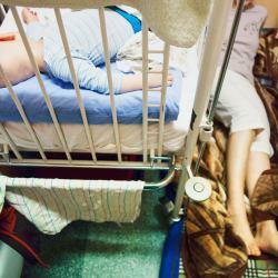 Matka leży pod łóżkiem chorego dziecka w szpitalnej sali
