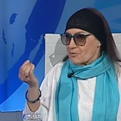 Temida Stankiewicz-Podhorecka w błęlitnym szalu, białej szacie i granatowej opasce na głowie