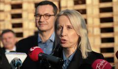Minister Teresa Czerwińska przed mikrofonem, w tle premier Mateusz Morawiecki