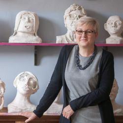 Ewa Radanowicz w jednej z pracowni swojej szkoły. Na ścianie za nią na półkach popiersia z gispu
