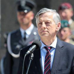 Andrzej Zybertowicz stoi przed mikrofonem wpatrzony w dal