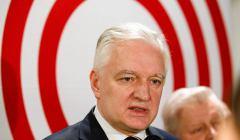 Jarosław Gowin na tle tarczy z białymi i czerwonymi okręgami