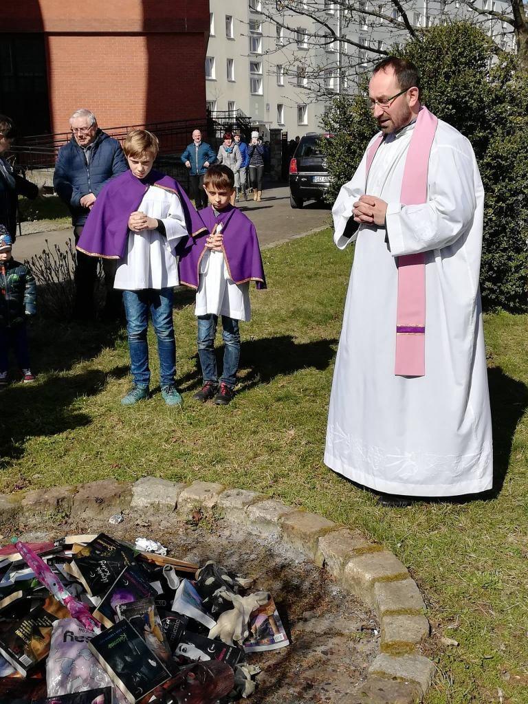Ksiądz w sztach liturgicznych w różowej stule nad ogniskiem z książkami i maskami