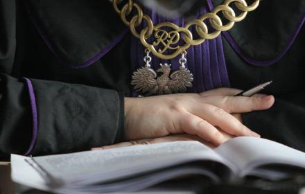 Sąd, akta na stole, w tle ręce sędziego i jego toga