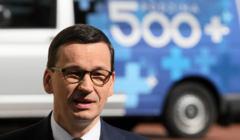 Mateusz Morawiecki na tle samochodu z logo 500+. Liczba urodzeń związana z tym programem spada. Kończy się efekt programu