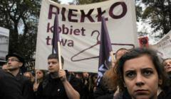 Czarny Piątek, kobieta trzyma plakat Piekło kobiet trwa