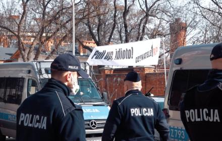 """Demonstracja pod siedzibą PiS w maseczkach i z transparentem """"Pull up, idioto!"""""""