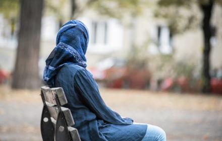 kobieta w chuście na głowie siedzi na ławce i patrzy w dal