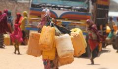 Somalia, kobieta niesie baniaki z wodą