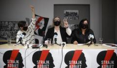 Trzy liderki Strajku Kobiet w czarnych maeczkach z błyskawicami pokazują znak V, siedząv przy stole z plakatami OSK